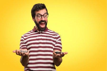 Hombre sorprendido con gafas que sostienen fichas de póquer sobre fondo colorido