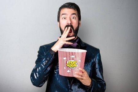 Handsome man with sequin jacket eating popcorns on grey background