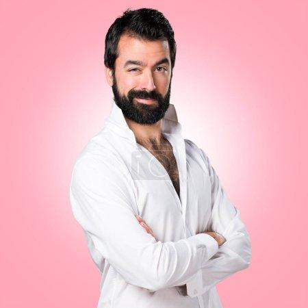 Foto de Hombre guapo con barba con sus brazos cruzados en colores de fondo - Imagen libre de derechos