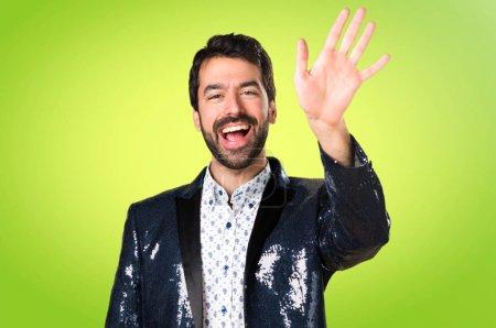 Photo pour Homme avec veste saluant sur fond coloré - image libre de droit