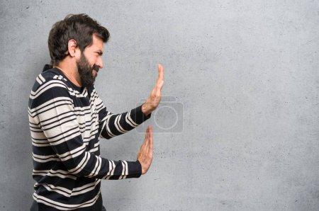 Homme à la barbe pousser quelque chose sur fond texturé