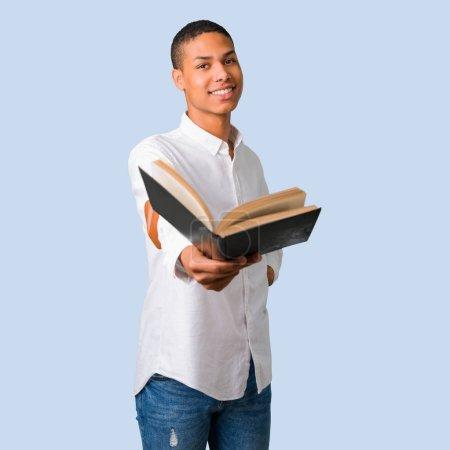 Photo pour Jeune homme afro-américain avec chemise blanche tenant un livre et le donnant à quelqu'un sur fond bleu isolé - image libre de droit