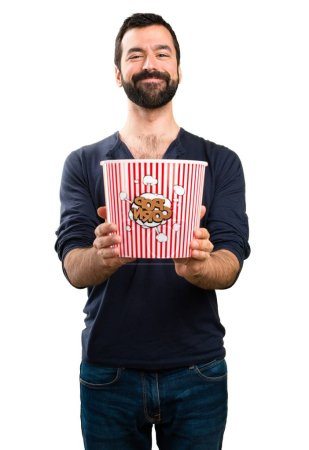 Handsome man with beard eating popcorns