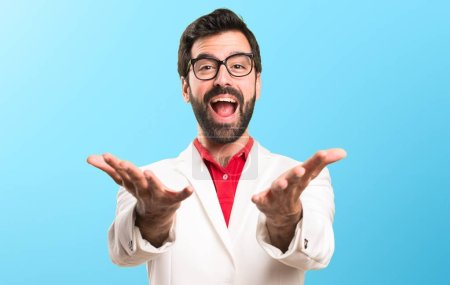 Brunette man with glasses presenting something on colorful background