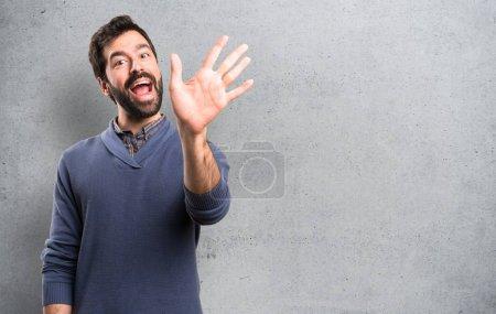 Photo pour Bel homme brune avec barbe saluant sur fond texturé - image libre de droit