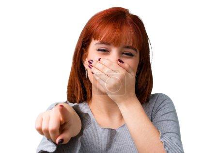 Photo pour Jeune fille rousse pointant du doigt quelqu'un et riant beaucoup - image libre de droit