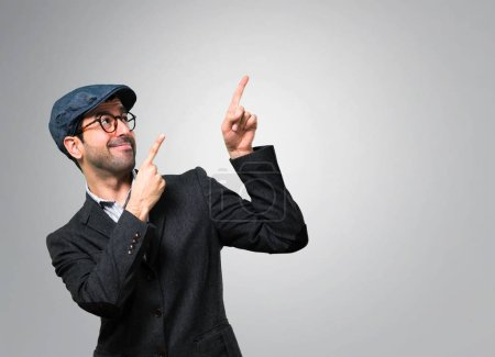 Handsome modern man with beret and glasses pointing with the index finger a great idea on grey background