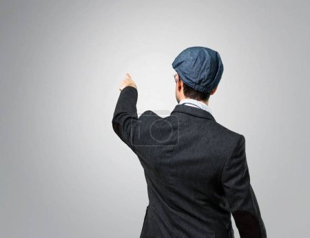 Handsome modern man with beret and glasses pointing back with the index finger on grey background