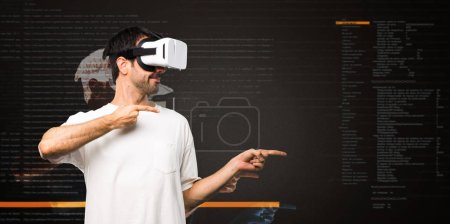 Photo for Man using VR glasses pointing finger to the side inside the virtual reality mode - Royalty Free Image