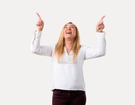 Photo pour Femme blonde du moyen âge avec chemise blanche pointant avec l'index une excellente idée et regardant vers le haut sur fond gris isolé - image libre de droit