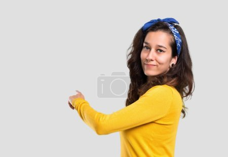 Young girl with yellow sweater and blue bandana on her head pointing back with the index finger presenting a product from behind on isolated grey background