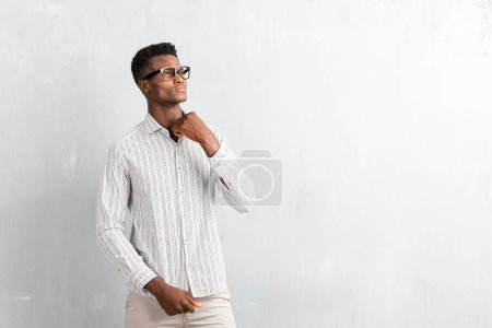 Young afro american man with glasses posing on textured grey wall