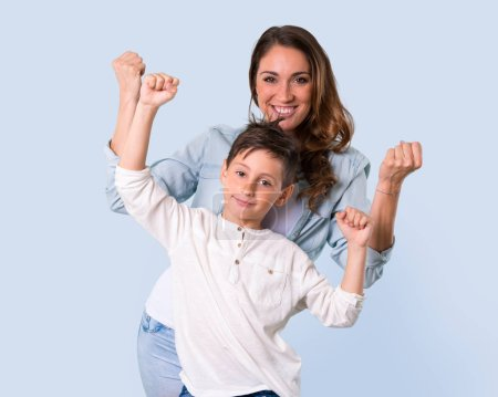 Photo for Mother and daughter celebrating a victory on blue background - Royalty Free Image