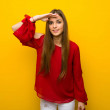 Young girl with red dress over yellow wall looking...