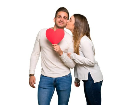 Photo for Couple in valentine day holding a heart symbol and kissing - Royalty Free Image