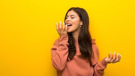 Photo pour Adolescente avec sweat-shirt rose sur fond jaune avec des oranges - image libre de droit