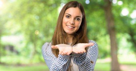 Photo pour Jeune fille avec chemise rayée tenant copyspace imaginaire sur la paume pour insérer une annonce à l'extérieur - image libre de droit