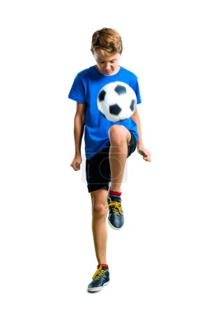 A full-length shot of Boy playing soccer on isolat...