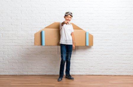 Photo pour Garçon jouant avec des ailes d'avion en carton sur son doigt arrière points à vous - image libre de droit