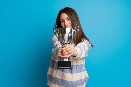 Photo for Young woman over blue wall holding a trophy - Royalty Free Image