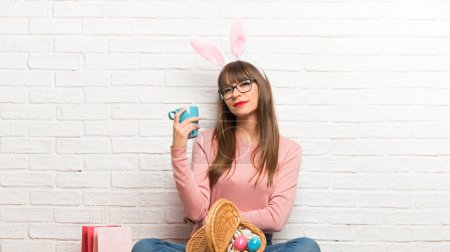 Woman with bunny ears for Easter holidays sitting on the floor taking a coffee in takeaway paper cup and smiling because he will start the day well