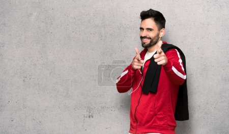 Photo for Handsome sportman pointing to the front and smiling over textured wall - Royalty Free Image