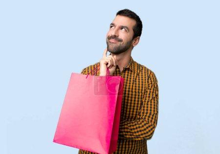 Photo pour Homme avec des sacs à provisions penser une idée tout en levant les yeux sur fond bleu isolé - image libre de droit