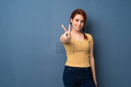 Photo for Young redhead woman over blue background smiling and showing victory sign - Royalty Free Image