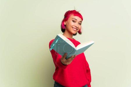 Photo pour Jeune femme avec un pull rouge tenant un livre et le donnant à quelqu'un - image libre de droit