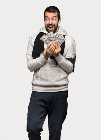 Photo for Sport man taking a lot of money over isolated grey background - Royalty Free Image