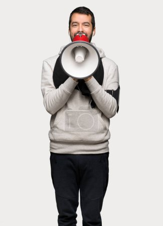 Photo for Sport man shouting through a megaphone to announce something over isolated grey background - Royalty Free Image