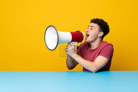 Photo pour Jeune homme avec mur coloré et table criant à travers un mégaphone - image libre de droit