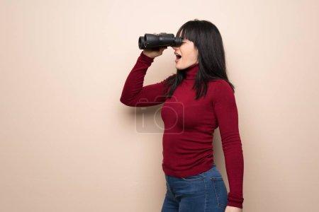 Photo pour Jeune femme au col roulé rouge et regardant au loin avec des jumelles - image libre de droit