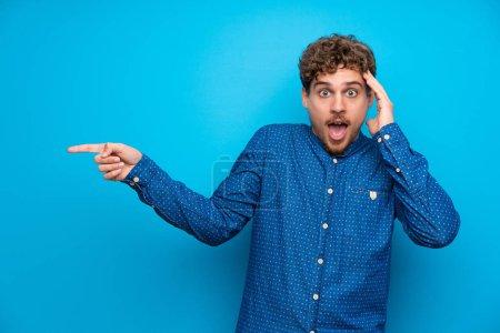 Photo pour Homme blond sur mur bleu isolé pointant du doigt sur le côté et présentant un produit - image libre de droit