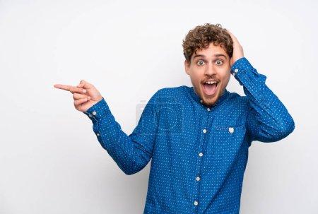 Photo pour Homme blond avec chemise bleue pointant du doigt sur le côté et présentant un produit - image libre de droit