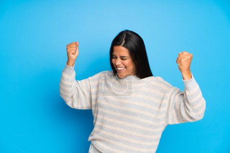 Photo for Young Colombian girl with sweater celebrating a victory - Royalty Free Image
