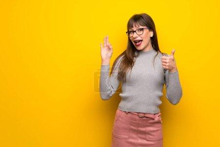 Photo pour Femme avec des lunettes sur le mur jaune montrant ok signe avec et donnant un pouce geste - image libre de droit