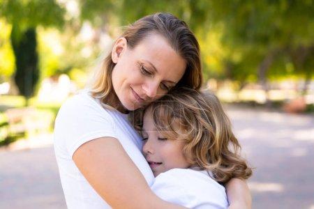 Photo pour Mère et fils dans un parc câlins et câlins - image libre de droit