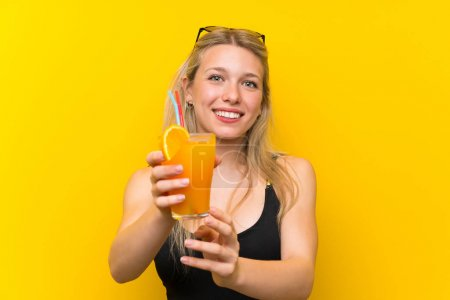 Young woman in swimsuit over yellow background wit...