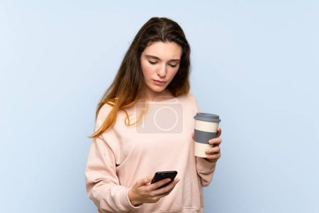 Young brunette girl over isolated blue background holding coffee to take away and a mobile