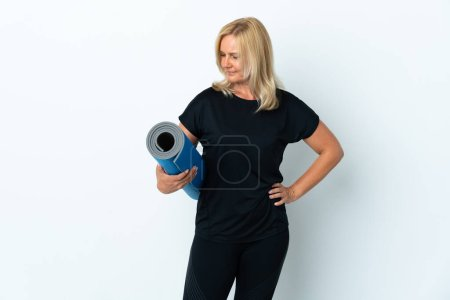 Middle age woman going to yoga classes while holding a mat isolated on white background with sad expression