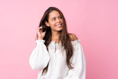 Young Brazilian girl over isolated pink background...