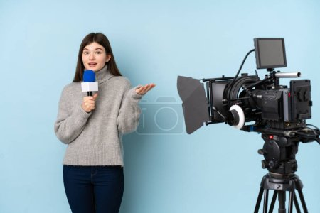 Photo for Reporter woman holding a microphone and reporting news over isolated blue background - Royalty Free Image