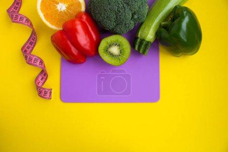 Photo pour Légumes, fruits et rose centimètre sur la planche à découper violet sur fond jaune. Vue de dessus. Espace copie. - image libre de droit