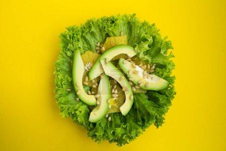 Photo pour Salade végétarienne à l'avocat, feuilles de laitue, orange et pignons de pin sur le fond jaune. Vue de dessus. - image libre de droit