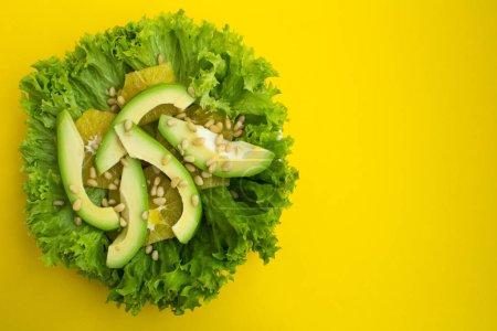 Photo pour Salade végétarienne à l'avocat, feuilles de laitue, orange et pignons de pin sur le fond jaune. Vue de dessus. Espace copie. - image libre de droit