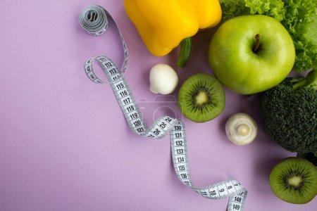Photo pour Légumes, fruits et centimètre blanc sur fond violet. Ingrédients des aliments sains. Vue de dessus. Espace copie. - image libre de droit