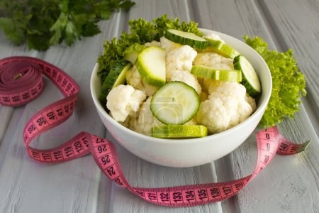 Photo pour Salade végétarienne aux légumes dans l'assiette blanche et rose centimètre sur le fond en bois gris - image libre de droit