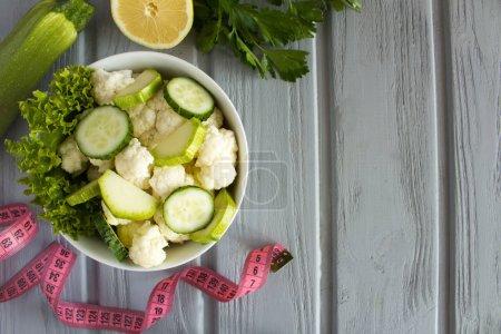Photo pour Salade végétarienne aux légumes dans la plaque blanche et rose centimètre sur le fond en bois gris. Vue de dessus. Espace copie. - image libre de droit