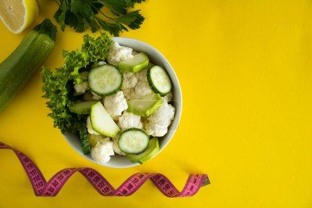 Photo pour Salade végétarienne aux légumes dans la plaque blanche et rose centimètre sur le fond jaune. Vue de dessus. Espace copie. - image libre de droit